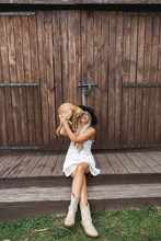 Young Woman In Black Hat, White Boho Dress And Cowboy Boots, Sitting Near An Old Barn And Holding In Hands Big Cute Red Cat. Countryside Life, Summer Holidays