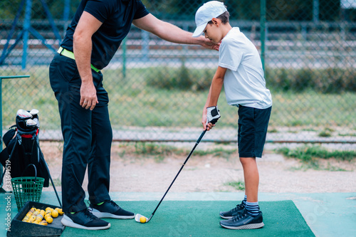 Fotografia Golf Lessons. Golf instructor giving game lesson to a young boy.