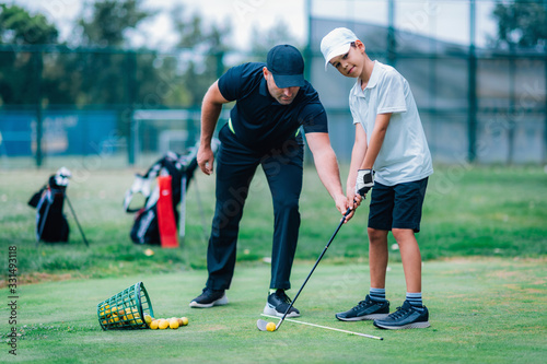 Fototapeta Personal golf lesson. Golf instructor with young boy on a golf driving range. obraz