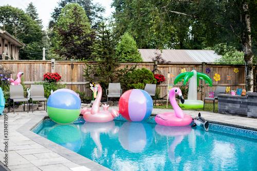 An inviting backyard pool full of hawaiin themed toys. Canvas Print