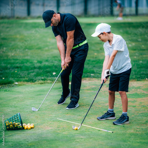 Fototapeta Golf Lessons. A golf Instructor and a boy practicing on a Golf Practice Range obraz