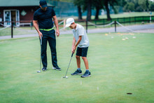 Learning Golf. Boy Practicing Putting With Instructor