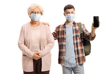 Elderly Woman And A Male Student Wearing Protective Medical Masks And Holding A Mobile Phone