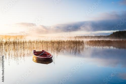 Photo Red boat on still misty lake at sunrise