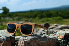 Pair Of Wooden Framed Aviator Style Sunglasses With Jigsaw Puzzle Piece Shapes Carved Into Ear Pieces, Placed On Rocks With Out Of Focus Background