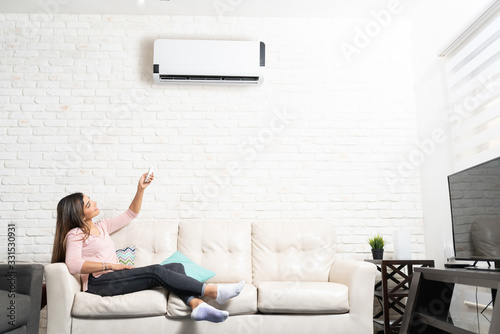 Photo Woman Turning on Air Conditioner At Home