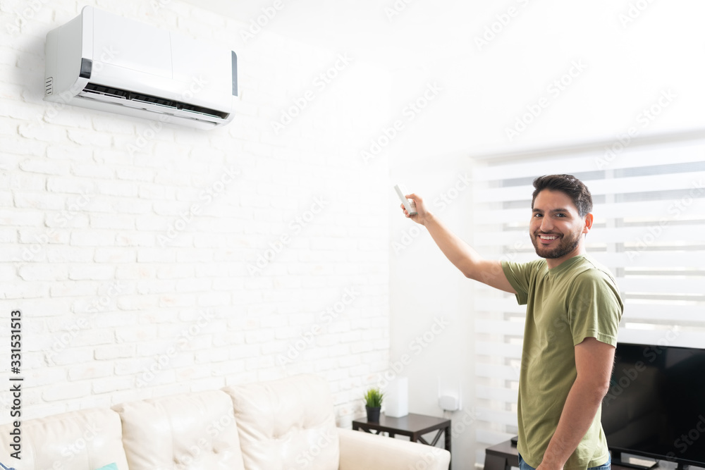 Fototapeta Man Adjusting Temperature Of Air Conditioner At Home