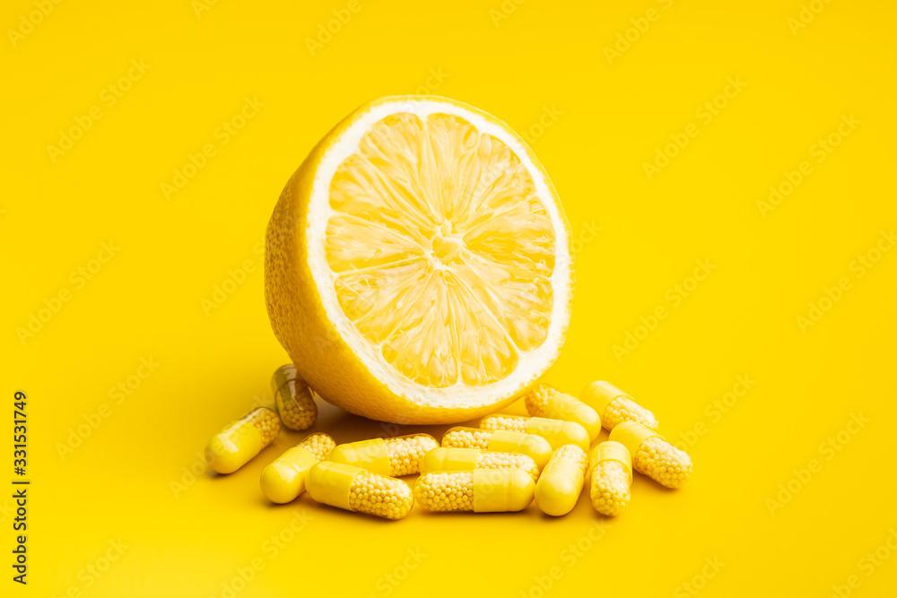 Fototapeta Vitamin capsules. Vitamin C pills and yellow lemon.