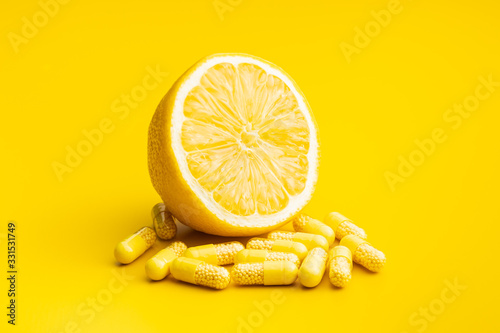 Fototapeta Vitamin capsules. Vitamin C pills and yellow lemon. obraz