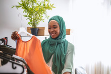 Everyone Do Shopping Online. Woman Packing Item That She Sells Online. Muslim Woman Designer As A Startup Business Owner. Female Muslim Designer Checking Hanged Clothes In Tailor Shop