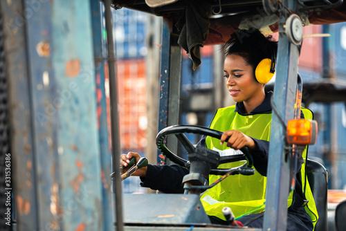 Fototapeta Female worker driving forklift in industrial container warehouse. obraz
