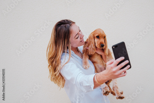 Photo young woman at the street with her cocker dog taking a picture with mobile phone