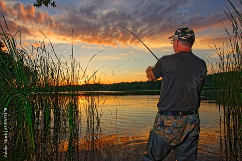 angler catching fish in the lake during sunset Wallpaper Mural