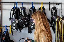 Girl Dressing Up With Scuba Diver's Equipment. Young Caucasian Girl Prepares Equipment For Diving, Checks The Oxygen Tank, And Holds The Regulator In Her Hands.