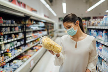 Shopping During An Epidemic.Buyer Wearing A Protective Mask.Nonperishable Smart Purchased Household Pantry Groceries.Pandemic Quarantine Preparation.Dry Goods And Nutritional Foods Shopping.Expiration