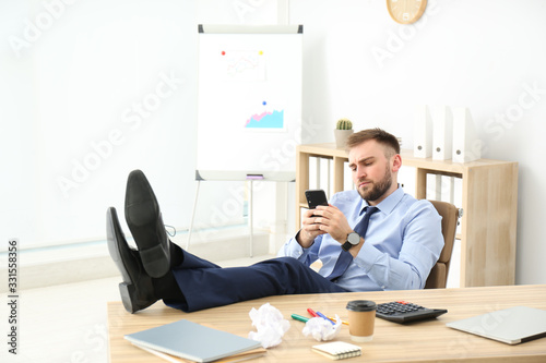 Photo Lazy office employee with mobile phone at workplace