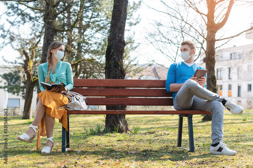 Fototapeta Woman and man in social distancing sitting on bench