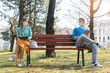 Woman and man in social distancing sitting on bench