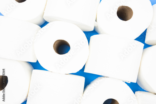 Background pattern of toilet paper rolls lay flat on the bright blue background Canvas Print