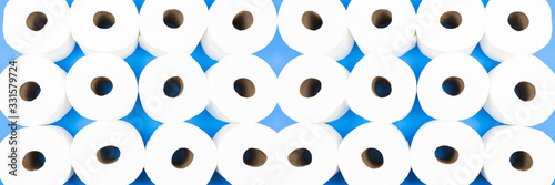 Background pattern mosaic of toilet paper rolls lay flat on the bright blue background Canvas Print