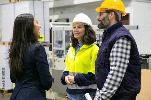Obraz Confident technicians talking with smiling office manager. Group of professional employees talking at manufacturing area. Communication concept - fototapety do salonu