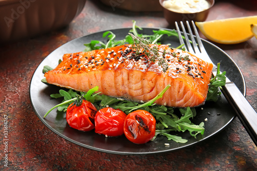 Plate with cooked salmon fillet on color background Fotobehang