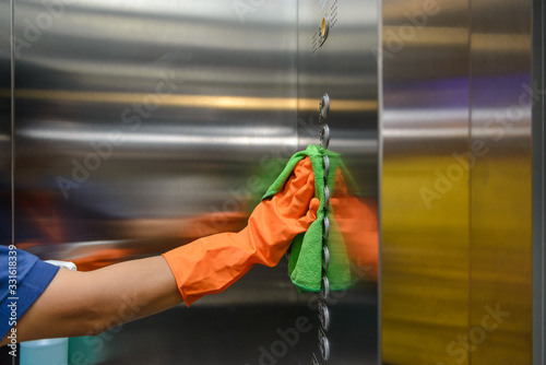 Fotografiet Woman hand in protective orange rubber gloves holding green microfiber cleaning