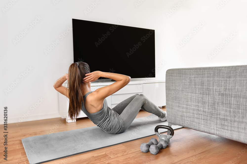 Fototapeta Home fitness workout class live stream online. Woman doing strength training abs situps bodyweight floor exercises watching videos on a smart tv in the living room of apartment.