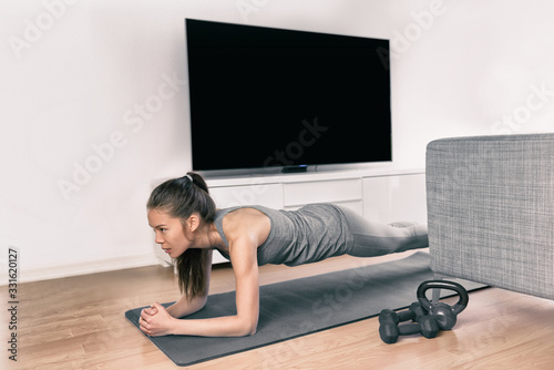 Fototapeta Fitness workout at home indoors. Asian girl doing plank exercises to exercise core watching tv videos of fit class. Young woman training muscles in front of the TV without going to the gym. obraz