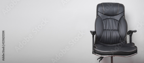 Black leather office chair in grey background. Canvas-taulu