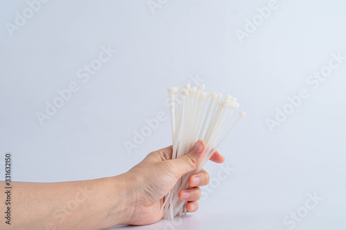 Fototapety, obrazy: Hand holding plastic tie clamps. Close up. Isolated on a white background.