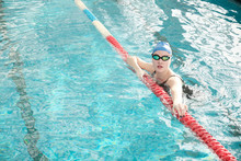 Portrait Of Healthy Young Woman In Goggles And Cap Hanging On Pool Lane Divider In Swimming Pool