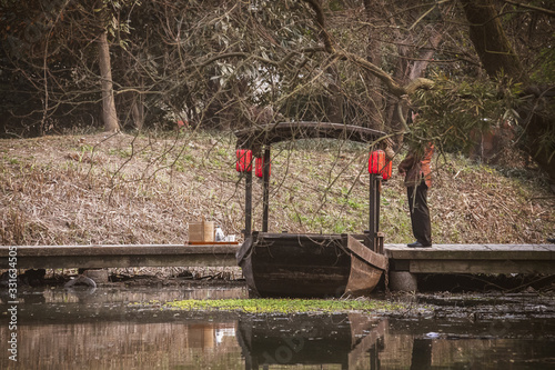 Fotografia chinese gondola, wooden sampan boat with red lanterns parked at jetty