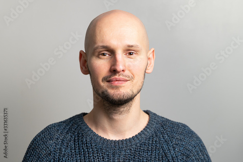 Carta da parati portrait of a young bald man in a knitted sweater on a gray background