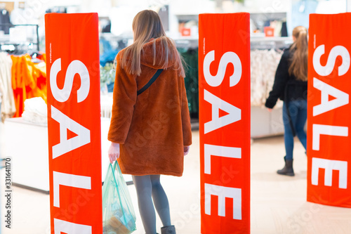 Photo Young woman goes through a security anti-theft framework in a store