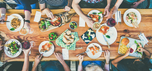 Fototapeta eating and leisure concept - group of people having dinner at table with food obraz