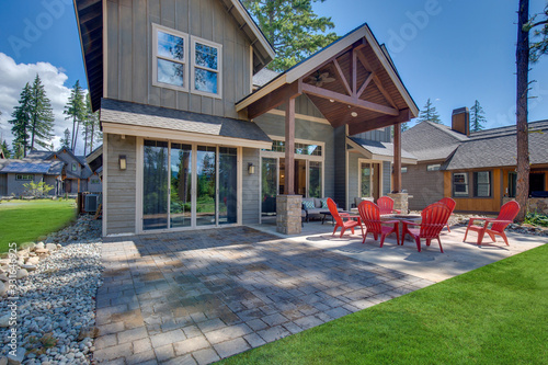 Obraz Back yard with fire pit and red chairs near newly bild luxury real estate home with forest biew and green grass. - fototapety do salonu