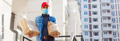 Fototapeta Delivery man holding paper bag with food on white entrance of house background ,
