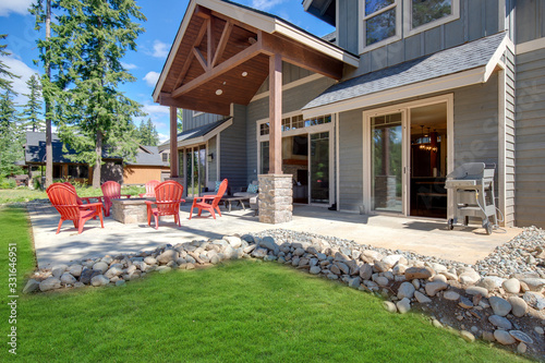 Back yard with fire pit and red chairs near newly bild luxury real estate home with forest biew and green grass. - fototapety na wymiar