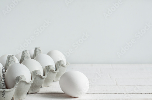 White raw chicken eggs in a cardboard box on a white background Wallpaper Mural