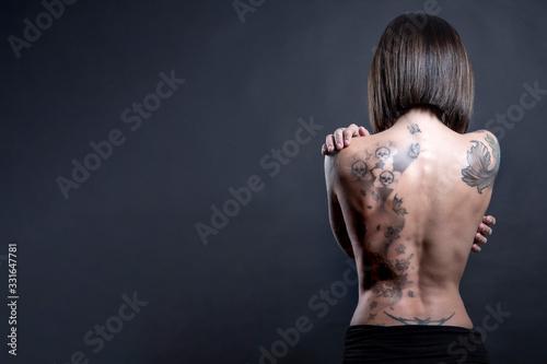 Donna con Schiena nudasi abbraccia con le mani con diversi tatuaggi , isolata su Canvas Print
