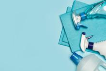 Productos De Limpieza: Botellas, Aerosoles,pulverizador, Paño Esponja Sobre Fondo Celeste Pastel. Vista Superior. Copy Space