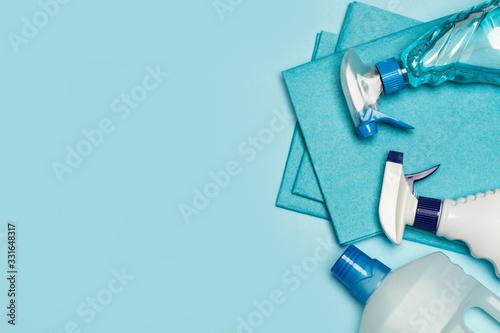 Fotografia Productos de limpieza: botellas, aerosoles,pulverizador, paño esponja sobre fondo celeste pastel