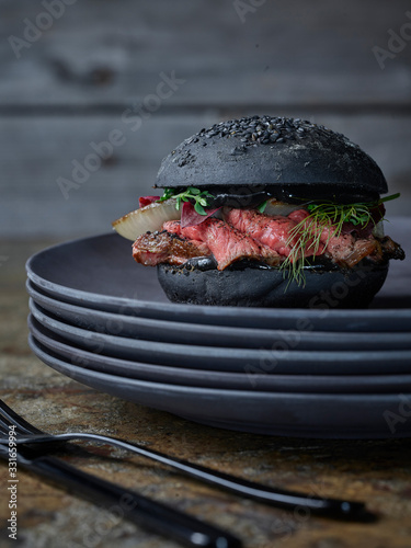 dark burger on plates with knife and fork  - 331659994