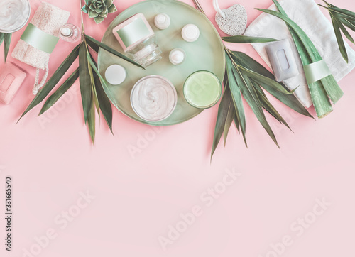 Modern beauty and skin care. Various natural cosmetic products with bamboo branches and aloe vera leaves. Eco friendly body care and spa accessories on pastel pink background. Zero waste . Top view