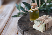 Concept Of Natural Ingredients In Cosmetology For Gentle Skin Care. Organic Olive Oil In Glass Bottle, Handmade Soap Bars. Atmosphere Of Serenity And Relax. Rustic Wooden Background, Close Up.