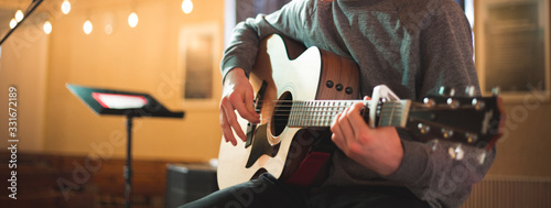 Fotografiet Young man playing on acoustic guitar