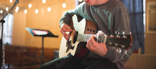 Young man playing on acoustic guitar Canvas Print