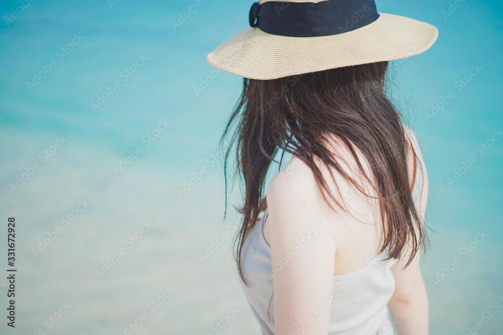 Fototapeta 沖縄の砂浜と麦わら帽子を被った女性
