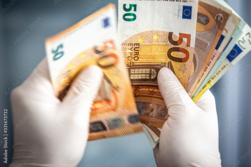 Fototapeta Man in surgical gloves holding Euro currency bills.